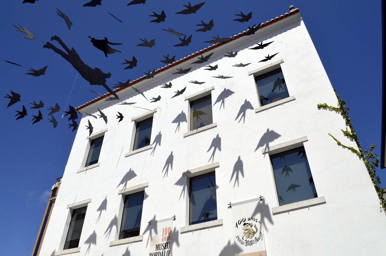 Fachada do Museu Bordalo Pinheiro, em Lisboa, com andorinhas refletidas na fachada