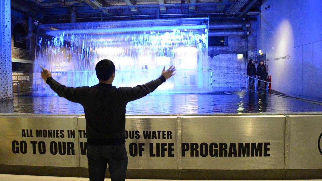 Visitante de braços abertos em frente a uma cascata de água na Fábrica Museu Guinness Storehouse, em Dublin