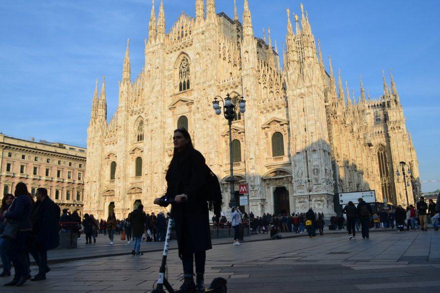 Turista anda de trotinete em frente à Catedral de Duomo em Milão, Itália. Foto de Diogo Pereira