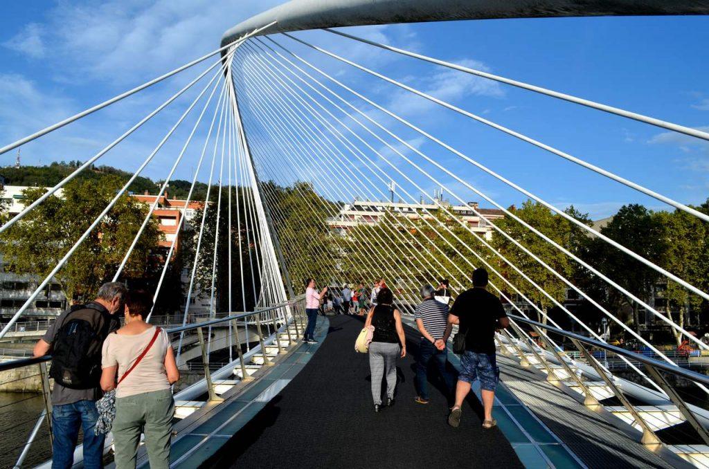 Várias pessoas atravessam a Ponte Zubizuri em Bilbau, Espanha