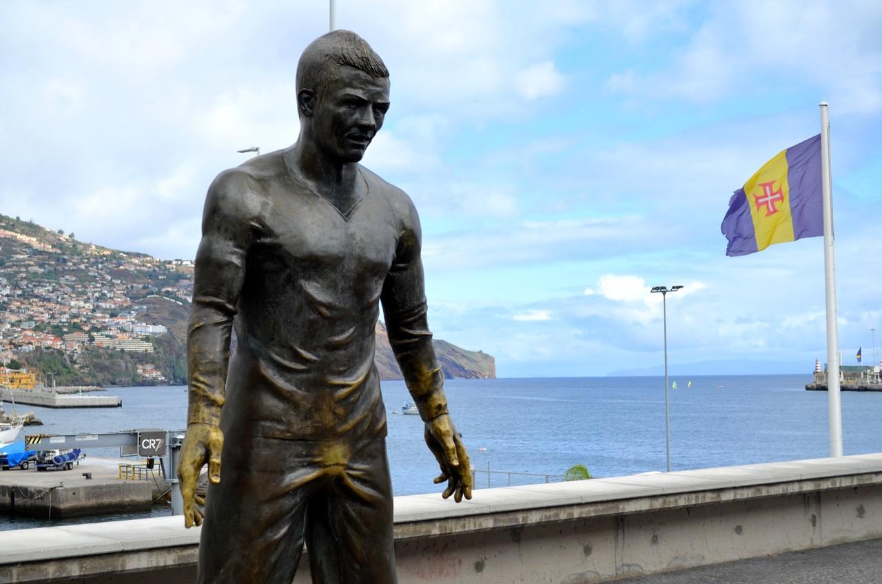 Estátua de Cristiano Ronaldo com bandeira da Madeira em fundo em frente ao CR7 Museu na Madeira