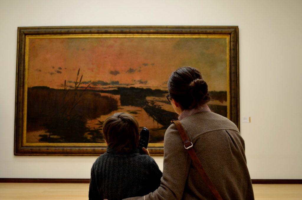 Criança observa obra de arte no museu José Malhos (Caldas da Rainha) com a ajuda de um audioguia