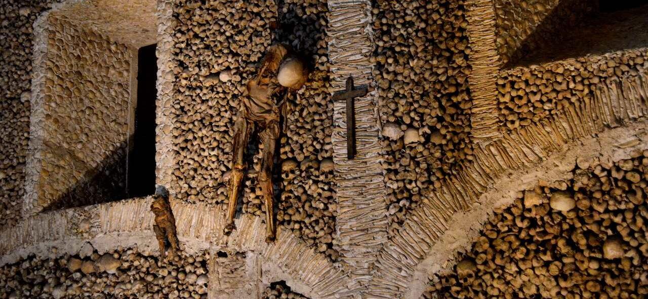 Esqueleto pendurado ao lado de uma cruz de cristo dentro da Capela dos Osssos de Évora