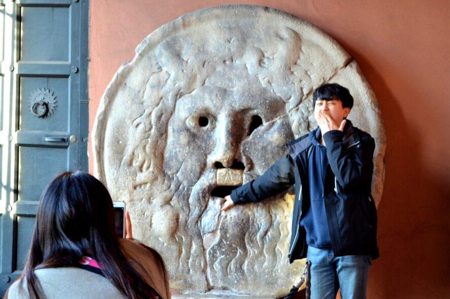 Turista coloca a mão na Boca da Verdade em Roma Itália