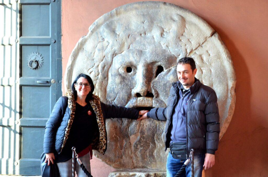 Dois turistas colocam as mãos na Boca da Verdade em Roma Itália