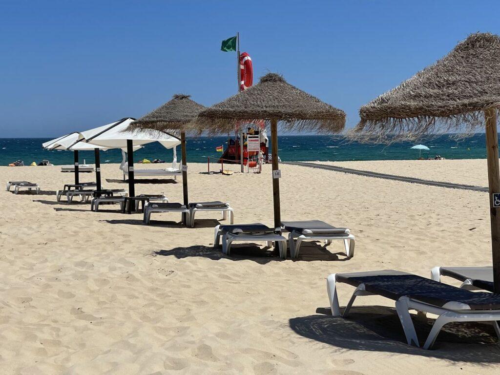 Bandeira verde e esperguiçadeiras na Praia da Ilha de Tavira
