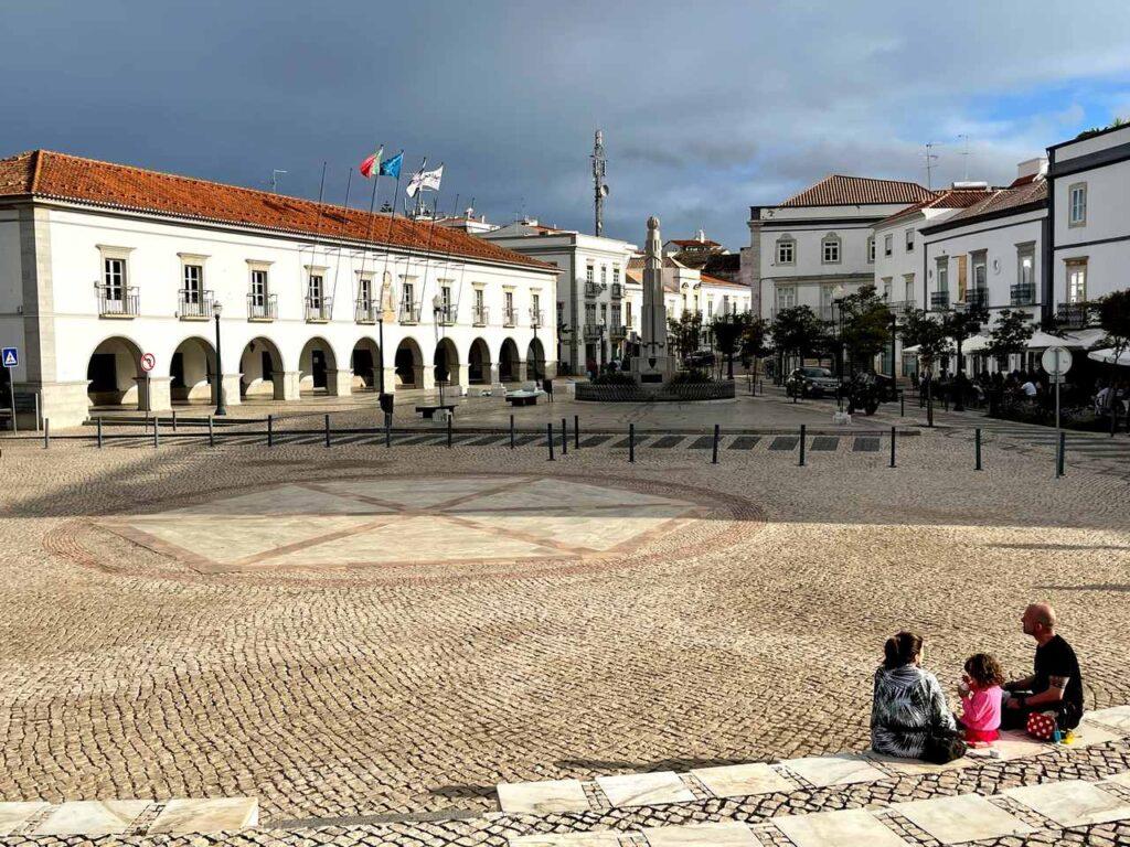 Família sentada no auditório da Praça da República de Tavira