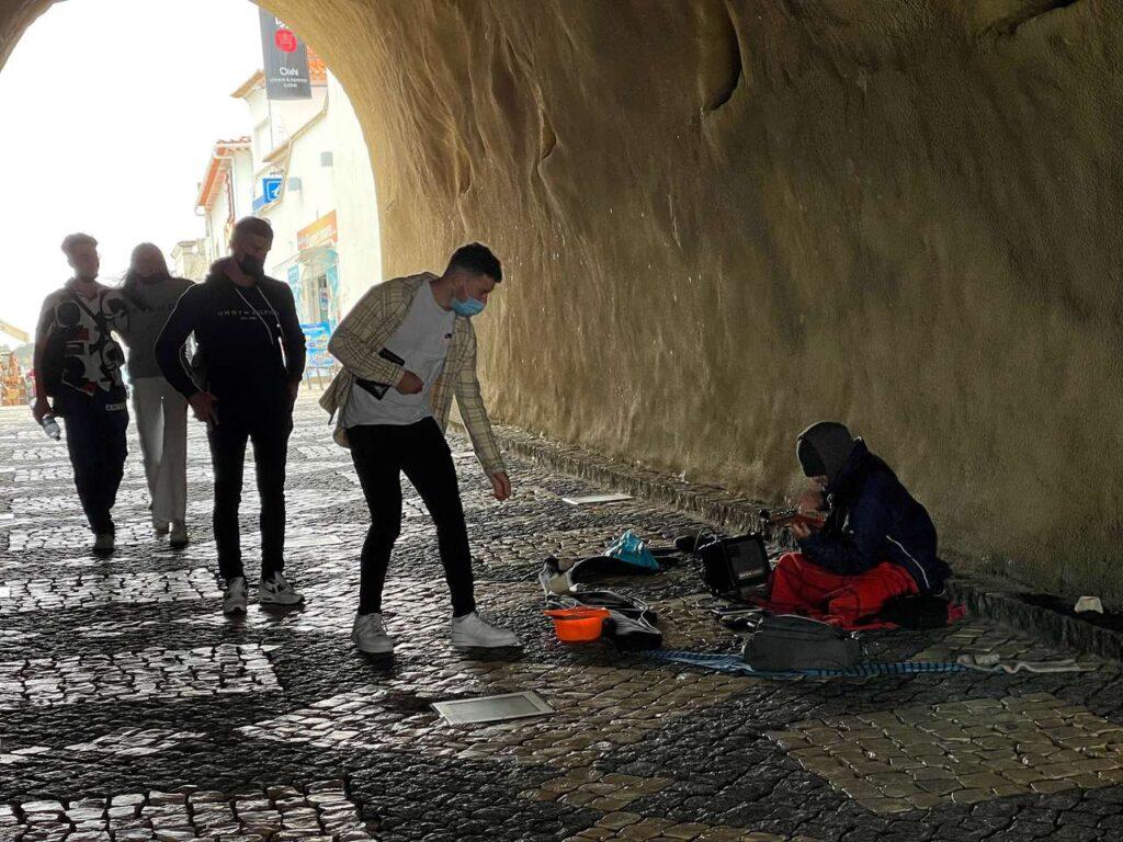 Turista dá uma moeda a um músico de rua que toca guitarra no túnel da Praia do Peneco em Albufeira